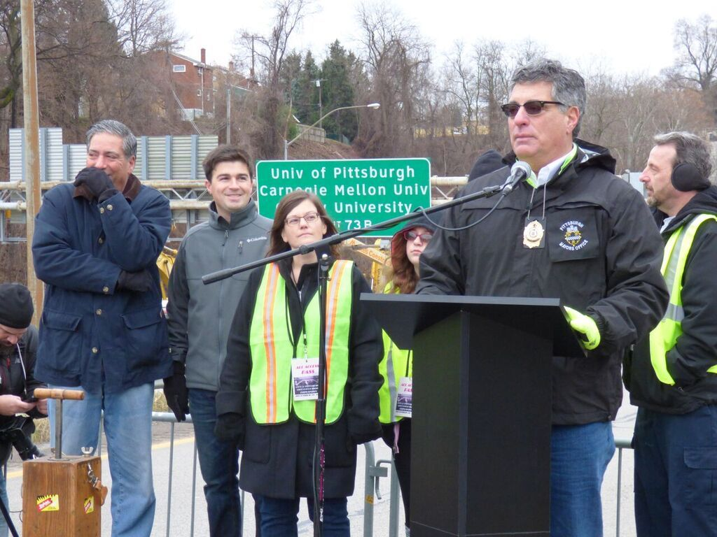 Corey O'Connor, Sally Schiedlmeier, Guy Costa at the podium remembering the bridge